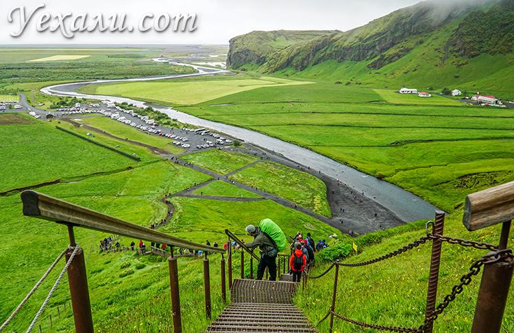 Туристы поднимаются на водопад Скоугафосс в Исландии.