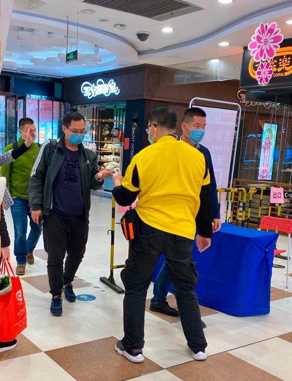 В торговых центрах Гуанчжоу, Китай, посетителям измеряют температуру